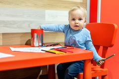 Cute little caucasian blond toddler boy sitting at table and drawing at children area at retail clothes store. Baby spending time stock photography