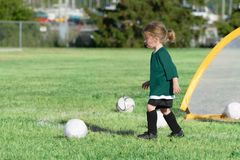 A cute little Caucasian blonde girl is running forward. The green field is on the background. stock photography