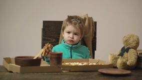 Cute little caucasian boy eating pizza at wooden table on which there are pizza box, spoon, dish and bear isolated on