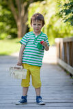 Cute little caucasian boy, eating strawberries in the park Stock Photo