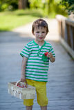Cute little caucasian boy, eating strawberries in the park Stock Image