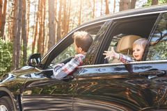 Cute little caucasian boy sitting inside the car and looking out the window. Family road trip. Caucasian child boy in checkered shirt looking out the window stock photo