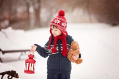 Cute little caucasian boy with teddy bear and red lantern, playi. Ng in the winter park, snowy day Stock Photography