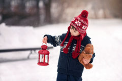 Cute little caucasian boy with teddy bear and red lantern, playi Stock Photo