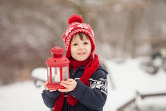 Cute little caucasian boy with teddy bear and red lantern, playi. Ng in the winter park, snowy day Stock Images