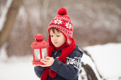 Cute little caucasian boy with teddy bear and red lantern, playi. Ng in the winter park, snowy day Royalty Free Stock Image