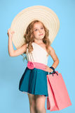 The cute little caucasian brunette girl in dress holding shopping bags Stock Image