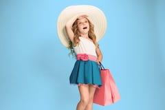 The cute little caucasian brunette girl in dress holding shopping bags Stock Images