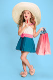 The cute little caucasian brunette girl in dress holding shopping bags Royalty Free Stock Image