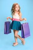 The cute little caucasian brunette girl in dress holding shopping bags Royalty Free Stock Photos