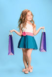 The cute little caucasian brunette girl in dress holding shopping bags Stock Images