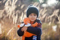 Cute little caucasian child, boy, holding fluffy toy, hugging it. In the park, on sunny winter day stock photo
