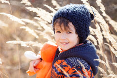 Cute little caucasian child, boy, holding fluffy toy, hugging it. In the park, on sunny winter day Stock Image