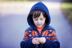 Cute little caucasian child, boy, holding fluffy toy, hugging it Stock Images