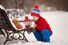 Cute little caucasian child, boy, holding fluffy toy, hugging it stock photography