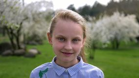 Cute little Caucasian girl with blue eyes in a beautiful shirt standing in the Park in springtime stock footage