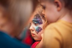 Girl with butterfly face painting. Cute little Caucasian girl having butterfly painted on her face during children birthday party stock images