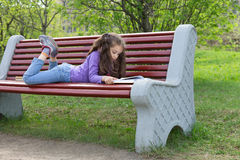 Cute little caucasian girl reading book lying on a bench in spring park Stock Images