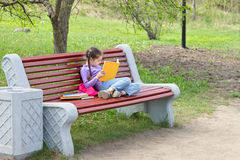 Cute little caucasian girl reading book sitting on a bench Stock Images