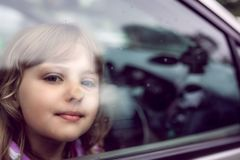 Girl looking through the car window. Cute little Caucasian girl sitting inside the car and looking through the window stock images