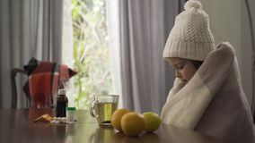 Cute little caucasian girl in warm white hat and scarf covering herself with a blanket. Child sitting at the table with. Pills, lemon and oranges. Concept of stock footage