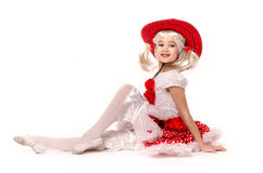 Cute little caucasian girl wearing red skirt, t-shirt with flowers and cowboy hat isolated on white background. Royalty Free Stock Images