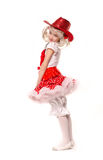 Cute little caucasian girl wearing red skirt, t-shirt with flowers and cowboy hat isolated on white background. She is dancing. Royalty Free Stock Photos