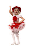 Cute little caucasian girl wearing red skirt, t-shirt with flowers and cowboy hat isolated on white background. She is dancing. Royalty Free Stock Image