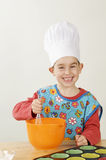 Cute little chef. A cute boy with a chefs hat making cake Royalty Free Stock Photo