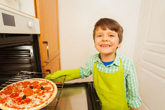 Cute little chef baking tasty pizza in the oven. Portrait of cute little chef, six years old boy, baking tasty pizza in the oven Royalty Free Stock Photos
