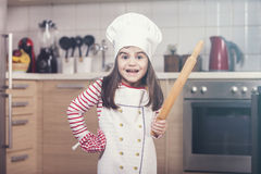 Cute little chef. Excited little girl chef in kitchen with rolling pin in hand Stock Image