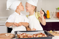 Cute Little Chef Kissing her Chef Sister. In the Kitchen. Very Happy Kids Stock Photo