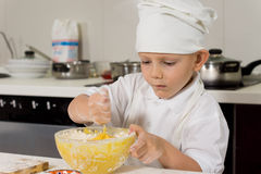 Cute little chef mixing ingredients as he bakes. Cute little boy chef in a white apron and toque standing at a kitchen table mixing ingredients in a bow as he Royalty Free Stock Image