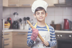 Cute little chef. Smiling boy cook holding a rolling pin Royalty Free Stock Photography