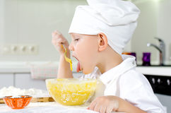 Cute little chef tasting his cooking. Cute little chef in a white toque and apron tasting his cooking as he mixes ingredients in a bowl Stock Photo