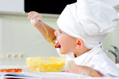 Cute little chef tasting his cooking. Cute little chef in a white toque and apron tasting his cooking as he mixes ingredients in a bowl Stock Photography