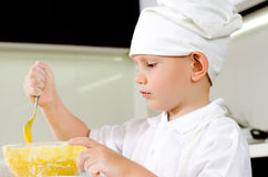 Cute little chef tasting his cooking. Cute little chef in a white toque and apron tasting his cooking as he mixes ingredients in a bowl Stock Images
