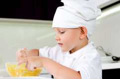 Cute little chef tasting his cooking. Cute little chef in a white toque and apron tasting his cooking as he mixes ingredients in a bowl Stock Photos