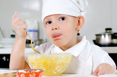 Cute little chef tasting his cooking. Cute little chef in a white toque and apron tasting his cooking as he mixes ingredients in a bowl looking thoughtfully into Stock Photo