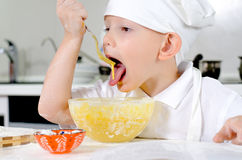 Cute little chef tasting his cooking. Cute little chef white toque and apron tasting his cooking mixes ingredients bowl looking thoughtfully into the air Stock Photography