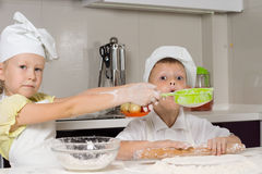 Cute Little Chefs Baking While Playing in Kitchen. Cute Little Chefs Baking Something to Eat While Playing in Kitchen Royalty Free Stock Image
