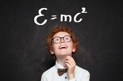 Cute little child boy against chalkboard background with science formulas in classroom.  royalty free stock photo