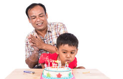 Cute little child boy blowing birthday cake royalty free stock photo