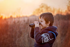 Cute little child, boy, exploring nature with binoculars Royalty Free Stock Images