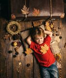 Cute little child boy are getting ready for autumn. Kid lies laying his hands behind head and resting on wooden floor in stock photos