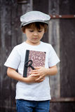 Cute little child, boy, holding big metal key and a book, willin Stock Photo