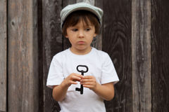 Cute little child, boy, holding big metal key, willing to unlock Royalty Free Stock Photos