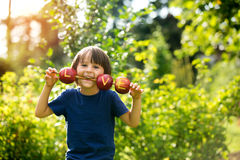 Cute little child, boy, holding a love sign, made from apples, l Stock Photos