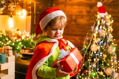 Cute little child boy play near christmas tree. Kid enjoy winter holiday at home. Home filled with joy and love. Merry stock photography