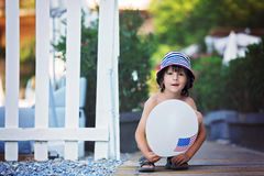 Cute little child, boy, playing with balloon with USA flag. Summertime outdoors Royalty Free Stock Photo